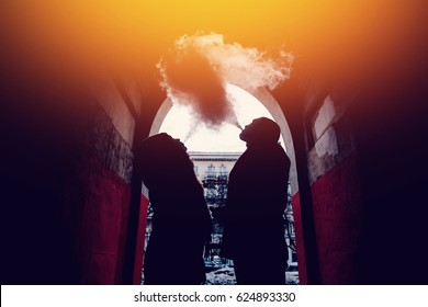 Young couple guy and girl are smoking couples from vape e-cigarettes on the street. Concept quit tobacco, give up cigarettes.