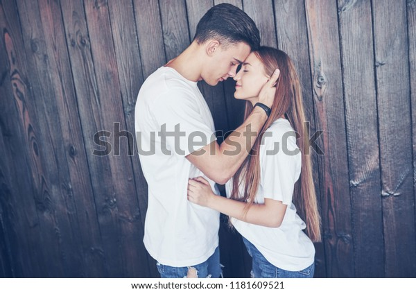 Young couple, guy and girl together on a wooden wall background. They are happy together and dressed alike. Always in a trend.
