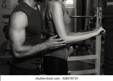 Young couple in the gym. Mutual support and assistance in the exercises. Work on your body. Photos for sporting and social magazines and websites.