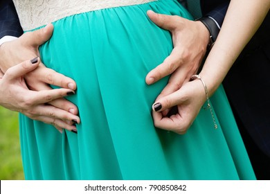 young couple hands close up on belly, pregnant woman