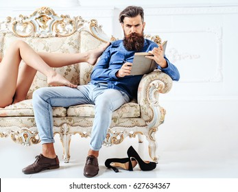 young couple of handsome bearded man in blue shirt and jeans with pretty cute girl or woman with sexy legs on luxurious vintage couch or sofa on white background, copy space
