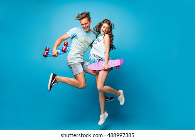 Young couple of handsome guy and pretty girl with long curly hair is jumping  on blue background in studio. They wear T-shirts, jeans short, hold skateboards in hands.