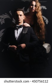 young couple of handsome man in black suit and bow with pretty sexy woman in elegant evening dress with skirt and long curly hair
