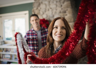 A young couple hanging tinsel up, decorating a house at Christmas