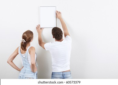 Young couple hangs framed on the wall