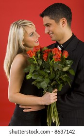 Young couple in happy hug. Womanan is holding bouquet of roses, smiling and looking at man. Side view