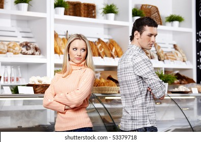 The young couple has turned away from each other in shop