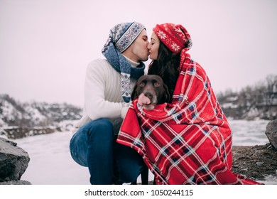 Young couple in hats and scarfs with dog wrapped in red plaid are sitting and kissing next to to frozen lake and rocks during winter walk.