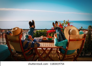 young couple have breakfast on balcony terrace with sea view