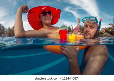 Young couple have a fun in swimming pool with cocktails