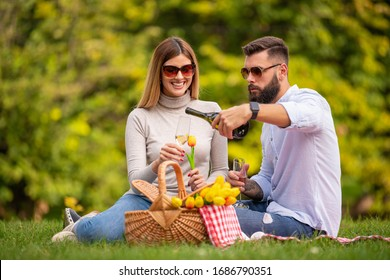 Young couple have picnic together in summer park.Portrait of happy couple enjoying a day in the park.