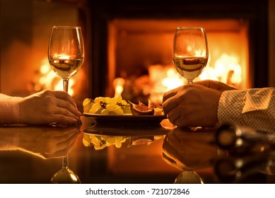 Young couple have romantic dinner with wine over fireplace background. Romantic concept .