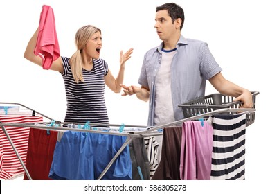 Young couple having an argument while hanging clothes on a clothing rack dryer isolated on white background