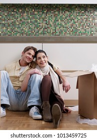 Young couple having a break while unpacking