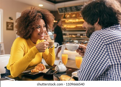 Young couple having a breakfast at cafe, drinking tea and orange juice, eating a croissant. They are looking at each other.