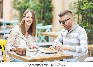 Young couple having a breakfast  in cafe outdoors