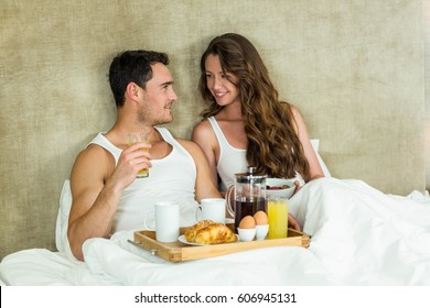 Young couple having breakfast on bed in bedroom