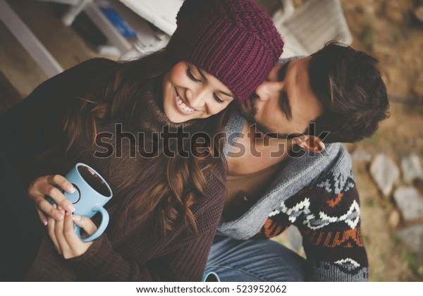 冬の外のロマンチックなキャビンで朝食をとる若い夫婦。