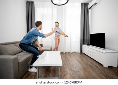 Young couple having a conflict switching a TV channel at home