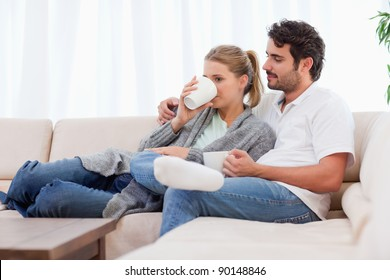 Young couple having a cup of tea in their living room