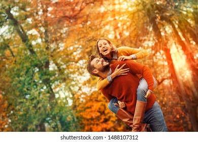 Young couple having fun in autumn park. Smiling young man carrying woman piggyback outdoor