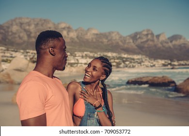 Young couple having fun at the beach. Happy african man and woman on a beach vacation.
