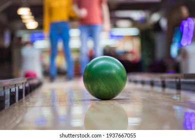 Young couple having fun in bowling alley.  Focus is on bowler.