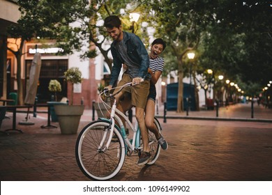 Young couple having fun in the city on bicycle. Happy young couple on bike ride.