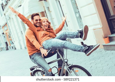 Young couple having fun in the city.Happy young couple going for a bike ride on a autumn day in the city.