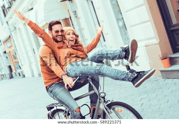 町で楽しい若い夫婦。町で秋の日に自転車に乗る幸せな若い夫婦。
