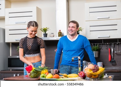 Young couple having fun in the kitchen preparing dinner