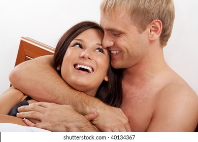 Young couple having fun and laughing in bed