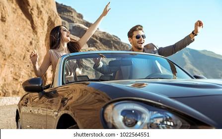 Young couple having fun on a beach in an convertible car