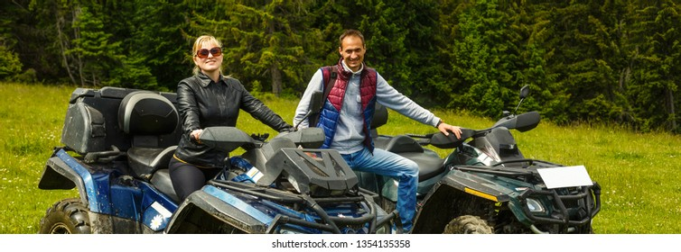 Young couple having fun on mountain while driving a quad bike on a summer day. Young man and woman on an ATV.