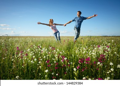 Young couple having fun on a green meadow with flowers