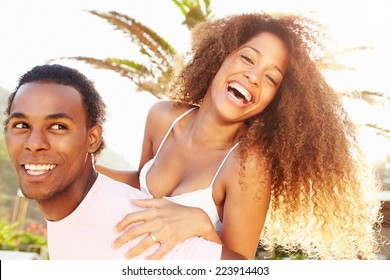 Young Couple Having Fun On Beach Holiday Together