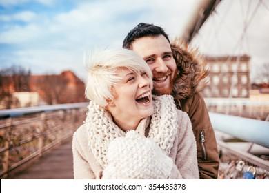 Young couple having fun on city footbridge. Krakow. Poland.