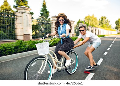 Young couple having fun on summer on road. Pretty girl with long hair driving a bike, handsome guy  keeps for a bicycle and rides on a skateboard. They look exited