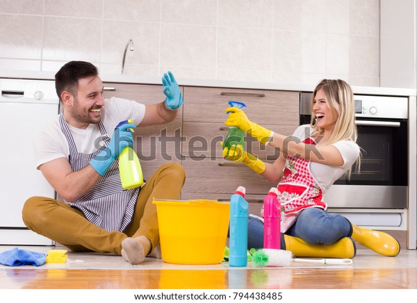 Young couple having fun on kitchen floor after finishing chores