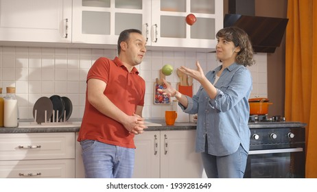 Young couple having fun playing juggling with apples in the kitchen. Happy couple playing the game of throwing apples.