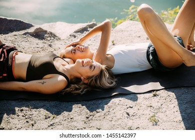 Young couple having fun at riverside in sunny day. Beautiful women exercizing yoga together on the nature. Concept of relationship, love, summer, weekend, honeymoon, healthy lifestyle.