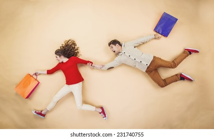Young couple having fun running with shopping bags against the beige background