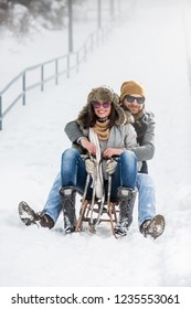Young couple having fun with sled on winter vacation