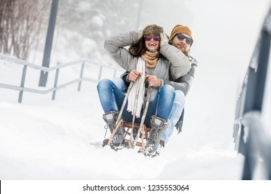 Young couple having fun with sled in snow