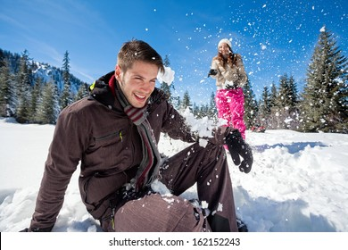 young couple having fun in snow,  outside