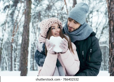 young couple having fun together in snowy forest