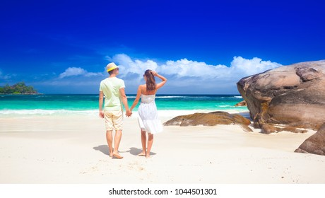 Young couple having fun at tropical Baie Lazare beach at Mahe island, Seychelles