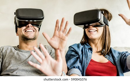 Young couple having fun with virtual reality goggles headset glasses -  Happy people playing game with new trends technology - Future concept - Focus on headsets