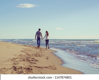 Young couple having fun walking and hugging on beach during autumn sunny day colored filter