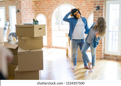 Young couple having fun wearing a monkey mask moving to a new apartment around cardboard boxes